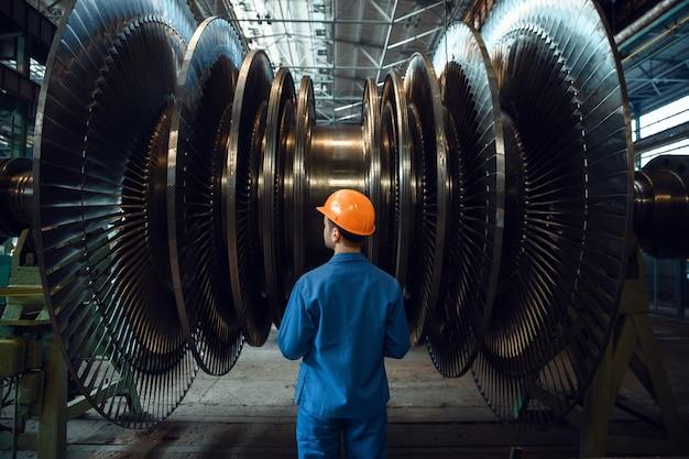 Mężczyzna sprawdza łopatki wirnika turbiny w fabryce