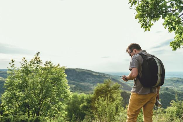 Mężczyzna sprawdza mądrze telefon w lesie