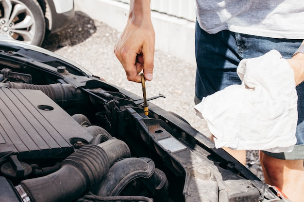 Mężczyzna sprawdza olej silnikowy w samochodzie