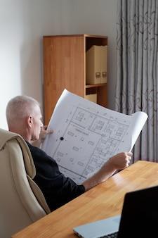Mężczyzna sprawdza plan budowy