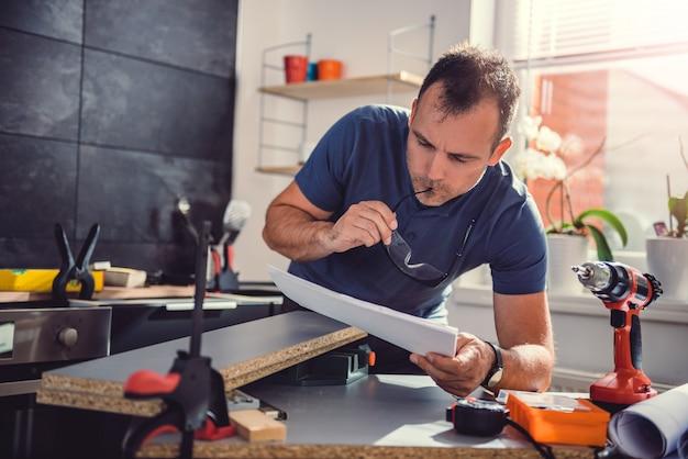 Mężczyzna sprawdza projekty podczas budowania kuchennych szafek