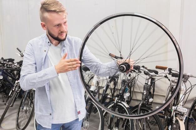 Mężczyzna sprawdza rowerowego obręcz w sporta sklepie