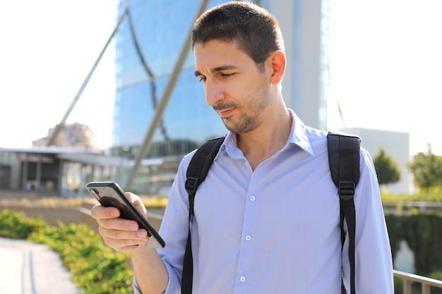 Mężczyzna sprawdza swój telefon komórkowy w nowoczesnym mieście