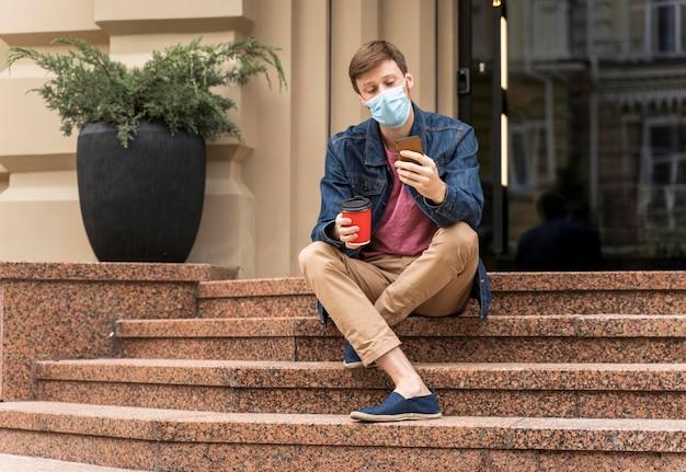 Mężczyzna sprawdza swój telefon siedząc na schodach