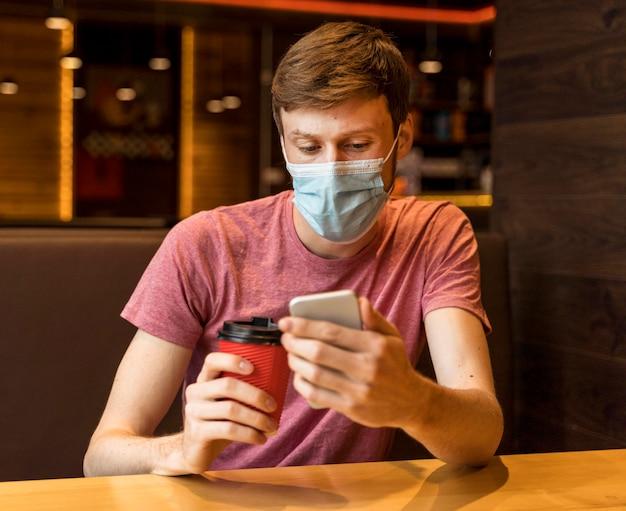 Mężczyzna sprawdza swój telefon w kawiarni