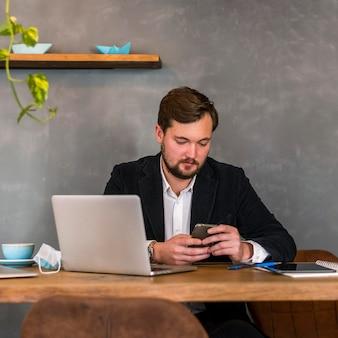 Mężczyzna sprawdza swój telefon w pracy