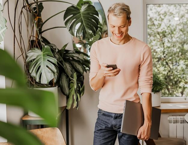 Mężczyzna sprawdza telefon, biznesmen z laptopem w obszarze roboczym w kawiarni eco z roślinami