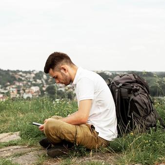Mężczyzna sprawdza telefon komórkowy z plecakiem