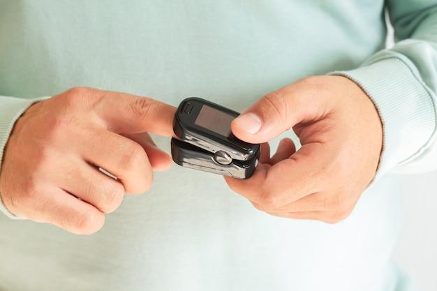 Mężczyzna sprawdza tlen we krwi za pomocą pulsoksymetru