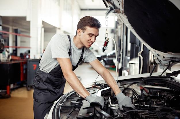 Mężczyzna sprawdza w swojej pracy silnik samochodu.