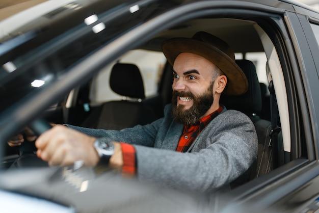 Mężczyzna sprawdza wnętrze nowego pickupa w salonie samochodowym. klient w salonie samochodowym, mężczyzna kupujący transport, firma dealera samochodowego dealer