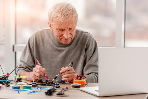 Mężczyzna sprawdzający doładowanie siedzi przy stole z narzędziami i laptopem podczas naprawy quadkoptera