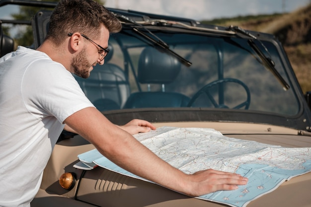 Mężczyzna sprawdzający mapę podczas podróży samochodem