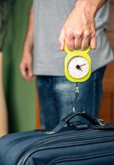 Mężczyzna sprawdzający wagę bagażu podręcznego za pomocą wagi stalowej zgodnie z ograniczeniami tanich linii lotniczych
