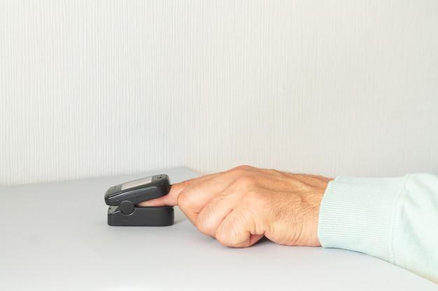 Mężczyzna sprawdzanie poziomu tlenu we krwi za pomocą pulsoksymetru w domu. koncepcja kontroli zdrowia