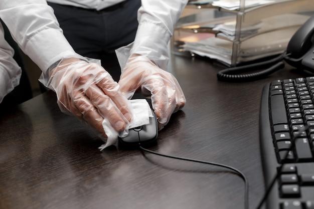 Mężczyzna sprzątający miejsce pracy używa papierowych serwetek
