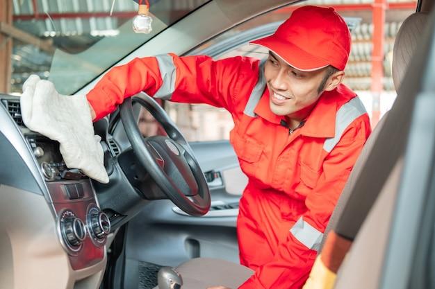 Mężczyzna sprzątający samochód w czerwonym mundurze wyciera deskę rozdzielczą wnętrza samochodu w salonie samochodowym