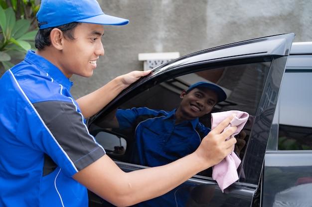 Mężczyzna sprzątanie samochodu pracownik usługi mycia czarny samochód