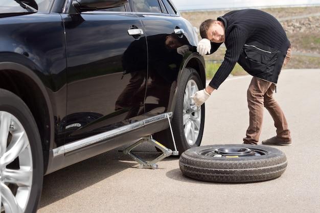 Mężczyzna stara się zmienić oponę w swoim samochodzie