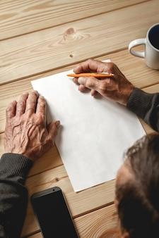 Mężczyzna stare ręce pisze na pustej kartce papieru