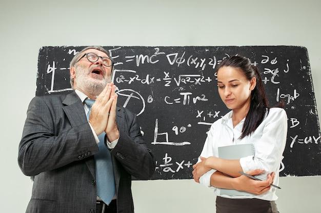 Mężczyzna starszy profesor i młoda studentka przed tablicą w klasie. koncepcja ludzkich emocji. modele kaukaskie. edukacja, uczelnia, uniwersytet, wykład, szkoła, koncepcje uczenia się