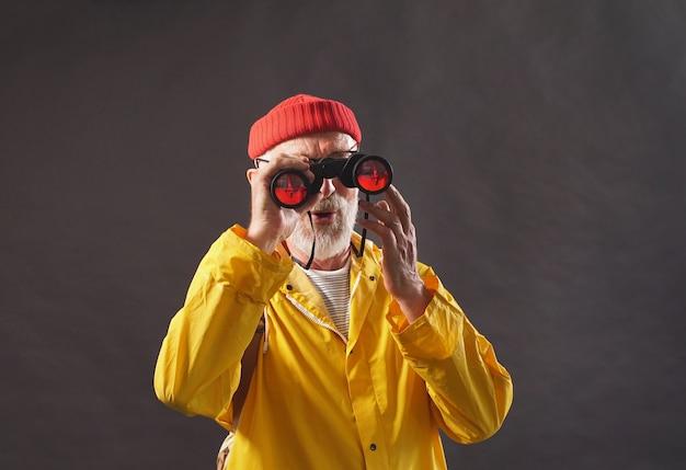 Mężczyzna, starzec, rybak, myśliwy, pozowanie na izolowanej ścianie, ubrany w żółty wodoodporny płaszcz przeciwdeszczowy