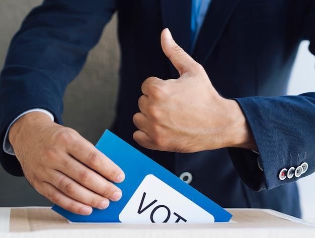 Mężczyzna stawia jego tajne głosowanie w pudełku