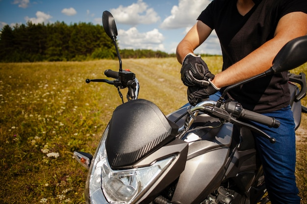 Mężczyzna stawia na rękawiczkach na motocyklu