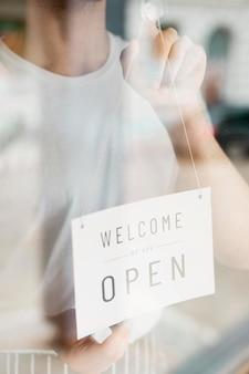Mężczyzna stawia w górę otwartego znaka na sklep z kawą okno
