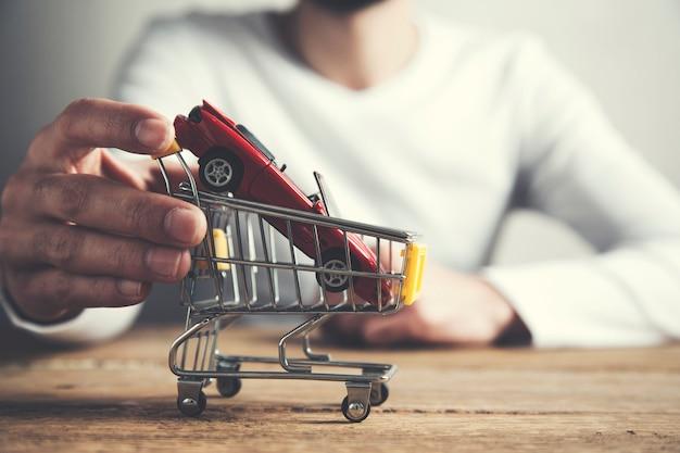 Mężczyzna stawia wzorcowego samochód na wózek na zakupy