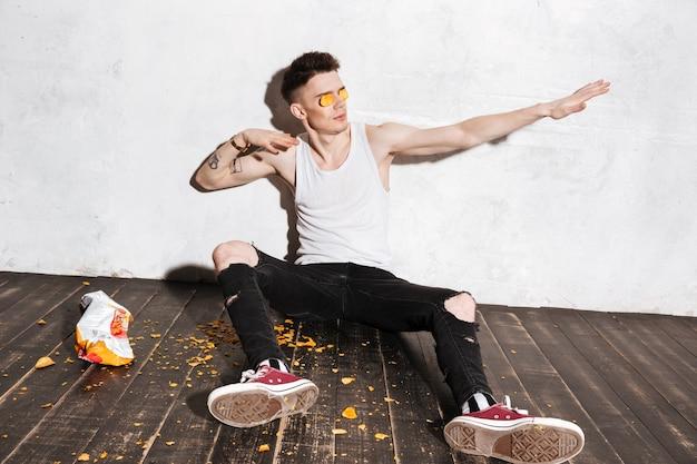 Mężczyzna stawiając chipsy ziemniaczane na jego oczy i zabawy