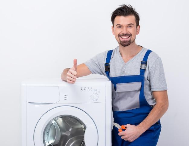 Mężczyzna stoi blisko pralki pokazuje aprobaty.