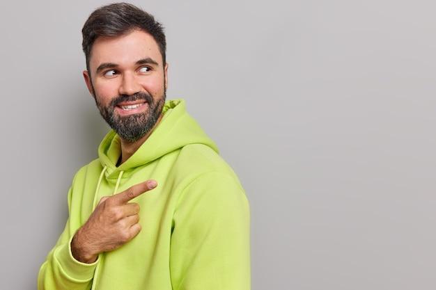 Mężczyzna stoi bokiem wskazuje z dala po prawej stronie sugeruje użycie tego miejsca na treści reklamowe nosi luźną bluzę z kapturem pozuje na szaro