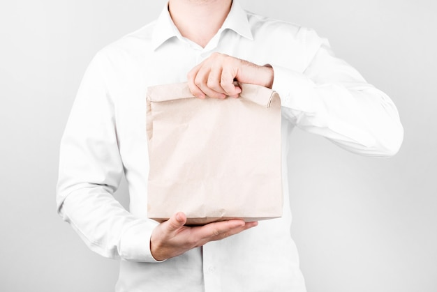 Mężczyzna stoi na białej ścianie w koszuli i dwiema rękami wyciąga papierową torbę zamiast plastikowej, koncepcja recyklingu, zakupów i ekologii