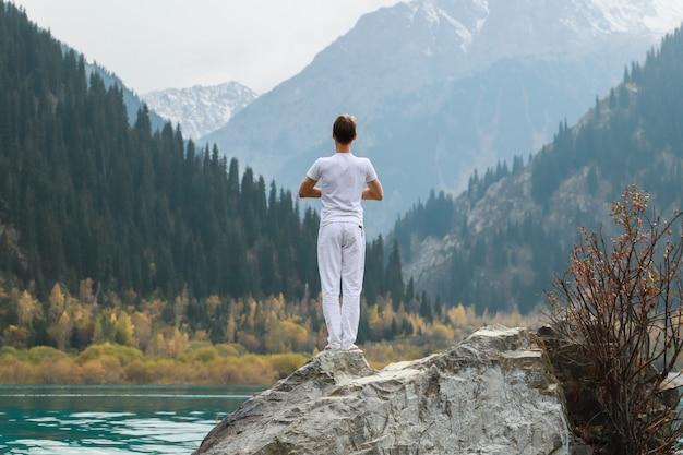 Mężczyzna stoi na kamieniu pośrodku górskiego jeziora i ćwiczy jogę. poza vrikshasaną.