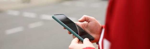Mężczyzna stoi na skrzyżowaniu z telefonem w ręku