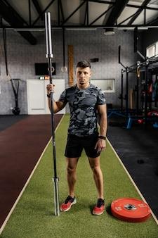 Mężczyzna stoi na środku siłowni i pozuje, trzymając sztangę w jednej ręce