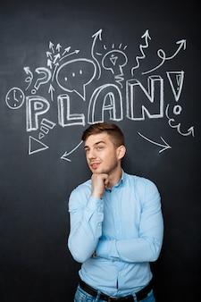 Mężczyzna stoi nad blackboard z planu pojęciem