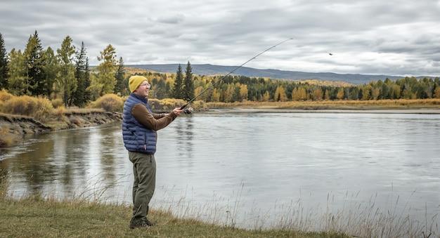 Mężczyzna stoi nad brzegiem rzeki w jesiennym lesie z wędką w rękach i łowi ryby