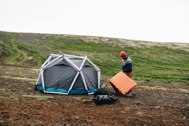 Mężczyzna stoi obok nowoczesnego namiotu w islandii