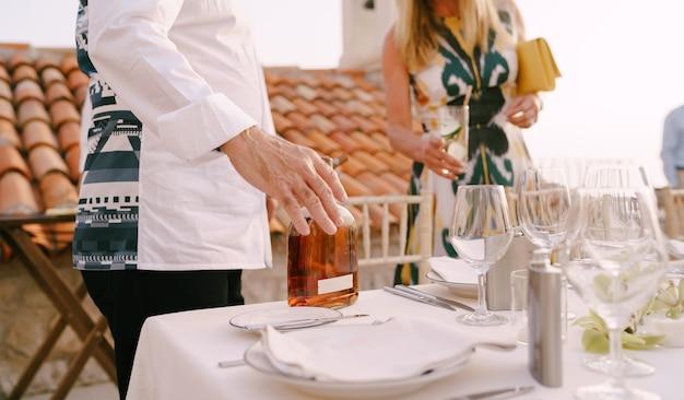 Mężczyzna stoi przy serwowanym stole i trzyma w ręku butelkę alkoholu na tle