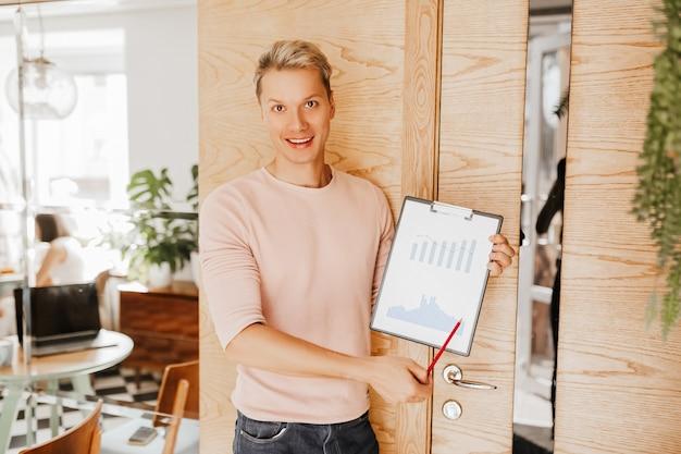 Mężczyzna stoi w biurze z dokumentami