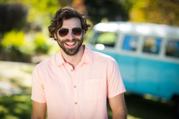 Mężczyzna stoi w parku w okularach przeciwsłonecznych