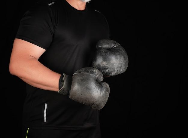 Mężczyzna stoi w stojaku bokserskim, w bardzo starych, czarnych rękawiczkach bokserskich