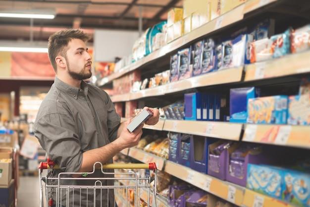 Mężczyzna stoi w supermarkecie z pakietem ciastek w rękach i patrzy na półkę ze słodyczami