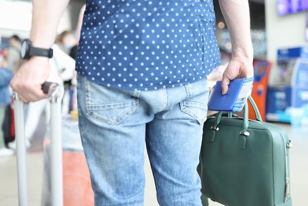 Mężczyzna stoi z bagażem w kolejce do odprawy samolotu na lotnisku i trzyma w ręku paszport z biletami