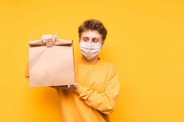 Mężczyzna stoi z paczką jedzenia z dostawy w dłoniach na masce medycznej na twarzy, patrzy w kamerę i pokazuje gest ok.