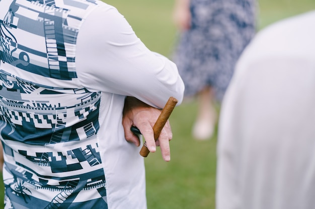 Mężczyzna stoi z rękami skrzyżowanymi na piersi i trzyma cygaro w dłoni zbliżenie widok z tyłu