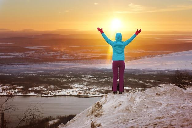 Mężczyzna stoi zimą na górze i podniósł ręce, witając słońce