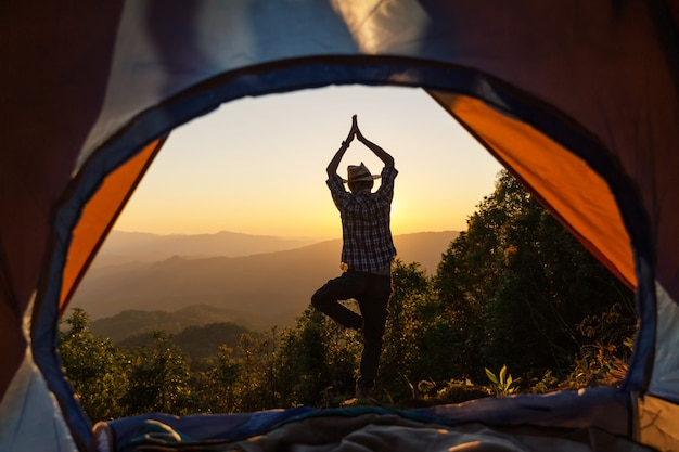 Mężczyzna stojący joga postawy przed namiotem kempingowym świecić się z wschodem słońca rano